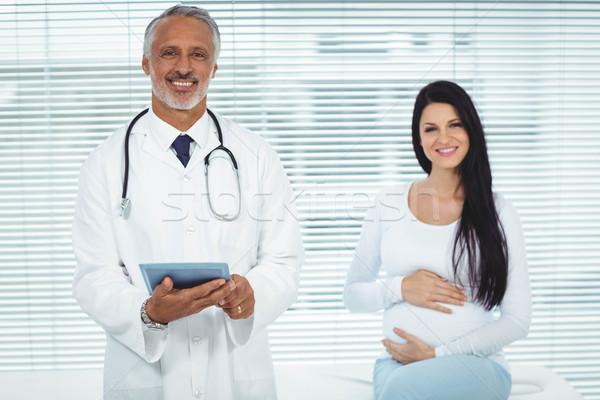 Doctor and pregnant woman smiling at camera Stock photo © wavebreak_media