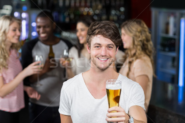 Glimlachend man tonen bier vrienden discotheek Stockfoto © wavebreak_media
