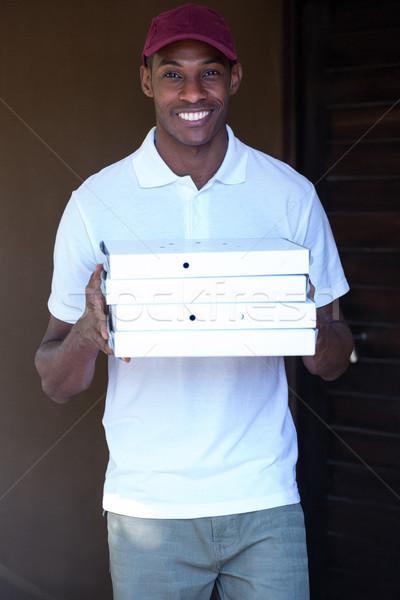 Happy delivery man holding pizza boxes  Stock photo © wavebreak_media