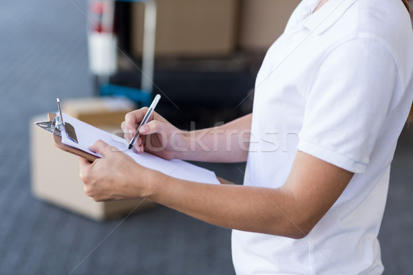 Close up of delivery woman is writing on a clipboard Stock photo © wavebreak_media