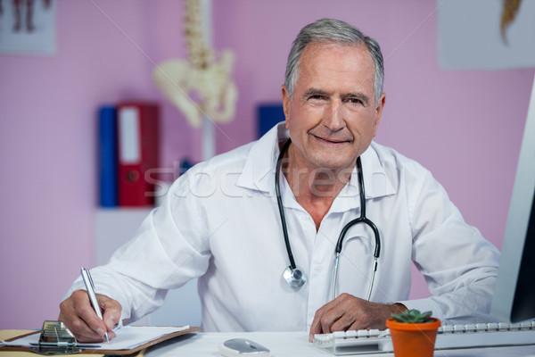 Physiotherapist writing on clipboard Stock photo © wavebreak_media
