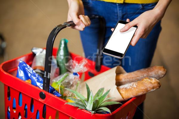 Mujer teléfono móvil supermercado Foto stock © wavebreak_media