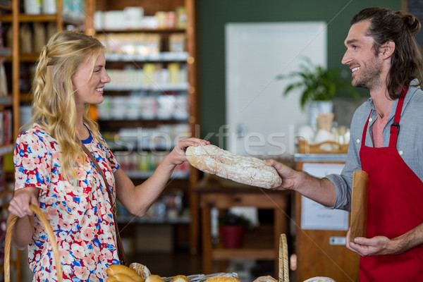Smiling male staff giving loaf of bread to woman Stock photo © wavebreak_media