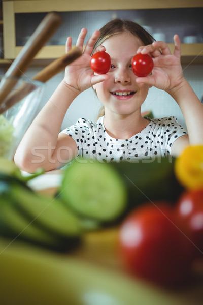 Playful girl holding cherry tomato on her eye Stock photo © wavebreak_media