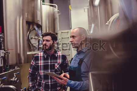 Confident owner standing with worker amidst machinery  Stock photo © wavebreak_media