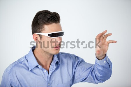 Man wearing protective eyewear pretending to touch an invisible object Stock photo © wavebreak_media