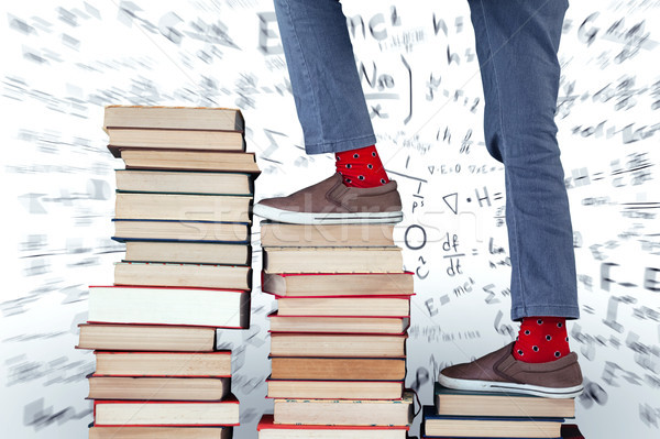 Low section of boy climbing stack of books against maths Stock photo © wavebreak_media