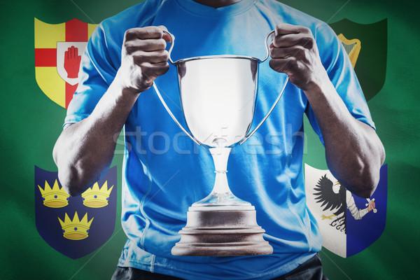 Composite image of mid section of sportsman holding trophy Stock photo © wavebreak_media