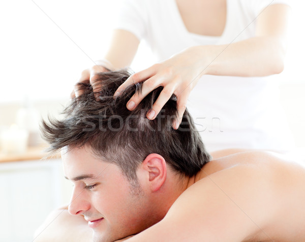 Happy young man receiving a head massage in a spa center Stock photo © wavebreak_media