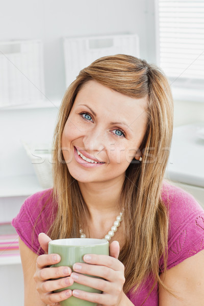 Portrait of a captivating woman holding a cup smiling at the camera in the kitchen Stock photo © wavebreak_media