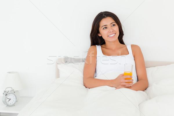 dark-haired woman holding orange juice sitting in bed looking at the ceiling in bedroom Stock photo © wavebreak_media