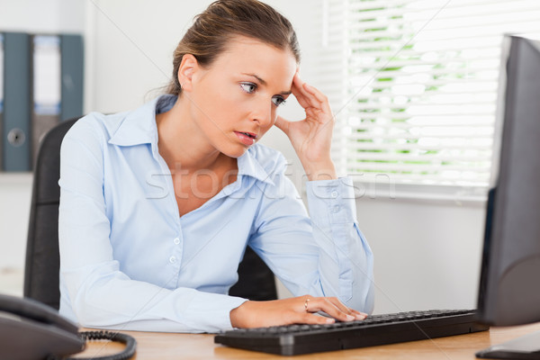 A frustrated businesswoman is looking to the screen of her pc in an office Stock photo © wavebreak_media