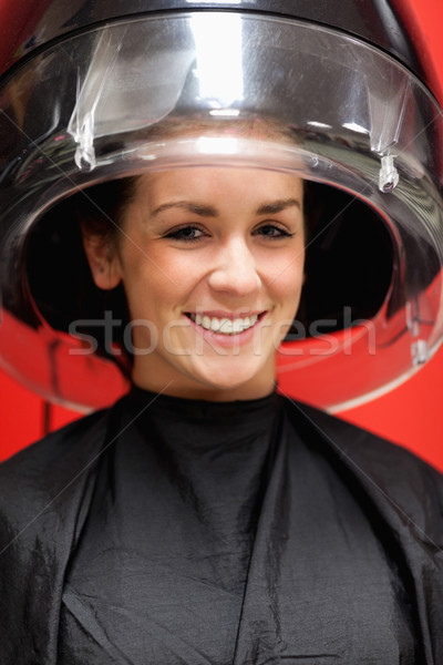 Portrait of a cute student under a hairdressing machine while smiling at the camera Stock photo © wavebreak_media