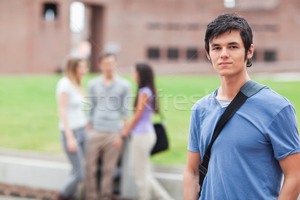 Handsome student posing while his classmates are talking in a yard Stock photo © wavebreak_media