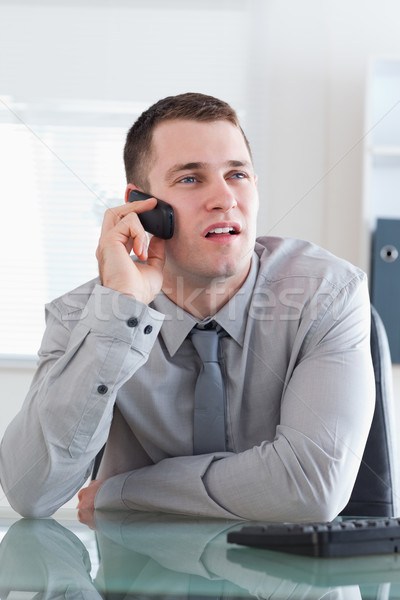 Young businessman looking at the screen while listening to the caller Stock photo © wavebreak_media