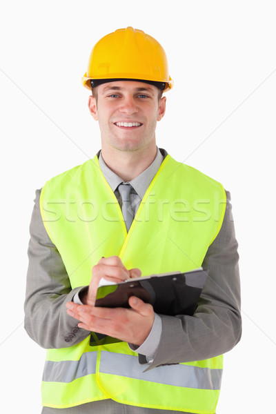 Portrait of a smiling builder taking notes while smiling at the camera Stock photo © wavebreak_media