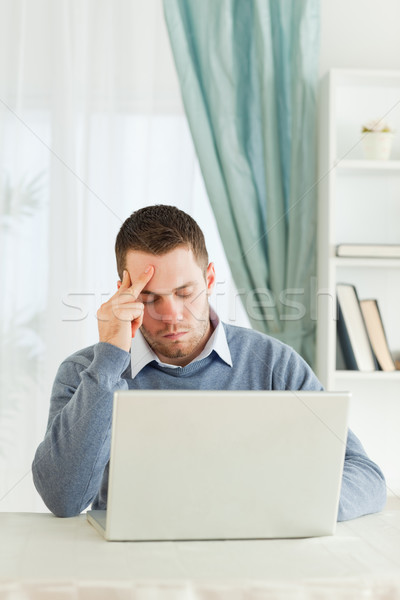 Worn out young businessman on his laptop Stock photo © wavebreak_media