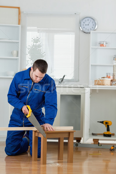 Portrait of a handsome handyman cutting a wooden board in a kitchen Stock photo © wavebreak_media