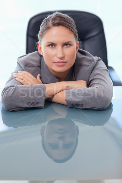 Portrait of a young businesswoman leaning on her desk while looking at the camera Stock photo © wavebreak_media