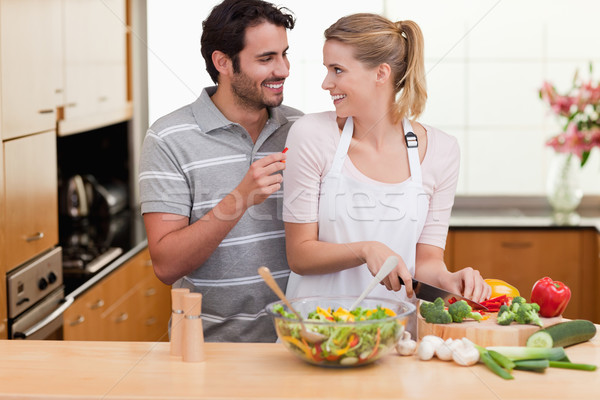 Young couple slicing vegetables in their living room Stock photo © wavebreak_media