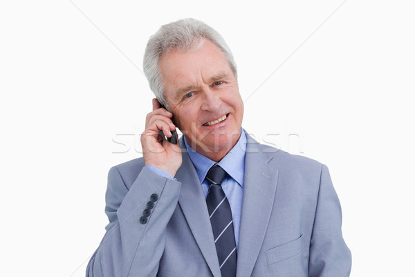 Close up of smiling mature tradesman on his mobile phone against a white background Stock photo © wavebreak_media