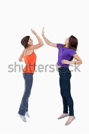 Smiling and dynamic teenagers jumping while giving a high-five Stock photo © wavebreak_media