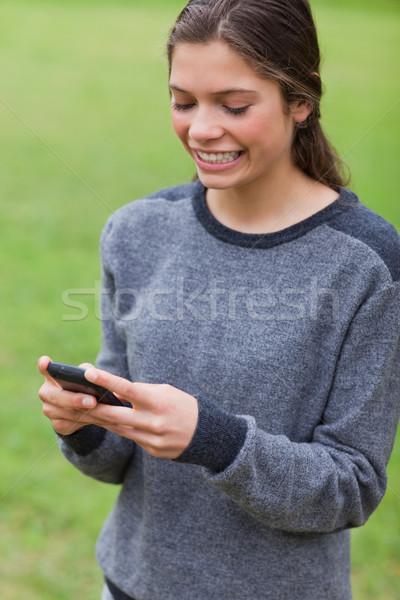 Fiatal lány mutat mosoly küldés szöveg mobiltelefon Stock fotó © wavebreak_media