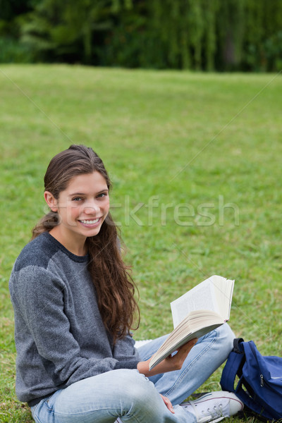 Young smiling girl sitting cross-legged on the grass while holding a book in a park Stock photo © wavebreak_media