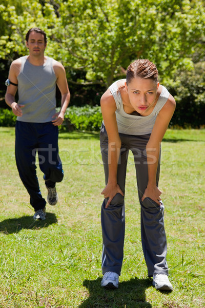 Woman bending over to recover while a man is jogging close to her in the background Stock photo © wavebreak_media