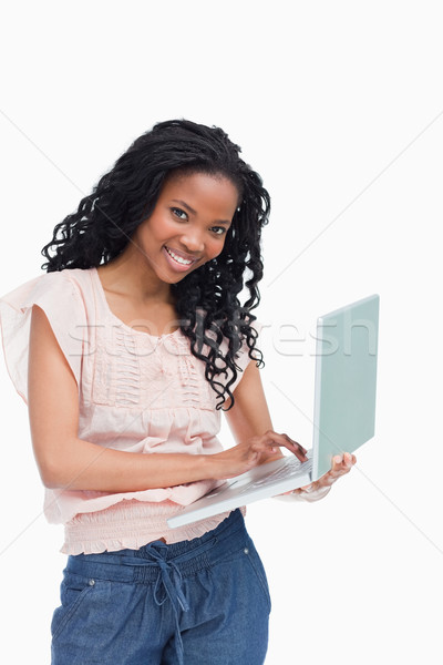 A young woman smiling at the camera is holding an laptop against a white background Stock photo © wavebreak_media