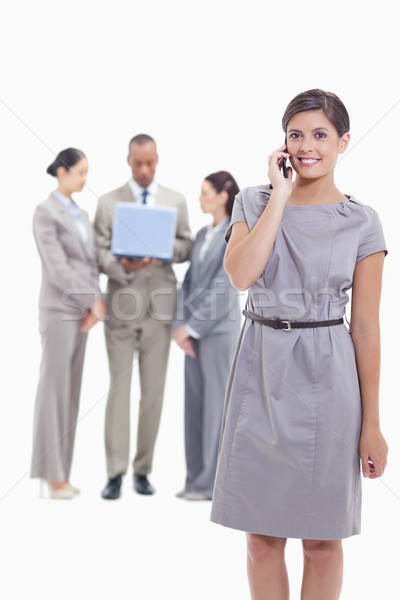 Businesswoman smiling on the phone and looking straight ahead with one arm along her body and co-wor Stock photo © wavebreak_media