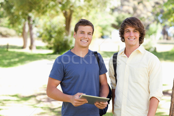 Stock photo: Close-up of two smiling male students with a touch pad in a park