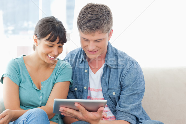 A smiling couple sitting together as they use a tablet pc  Stock photo © wavebreak_media