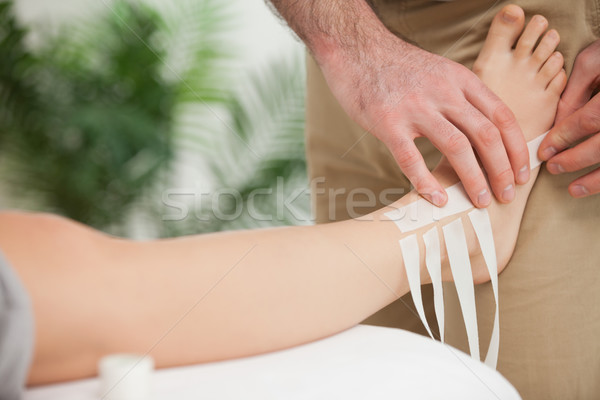 Doctor dressing an ankle in a room Stock photo © wavebreak_media