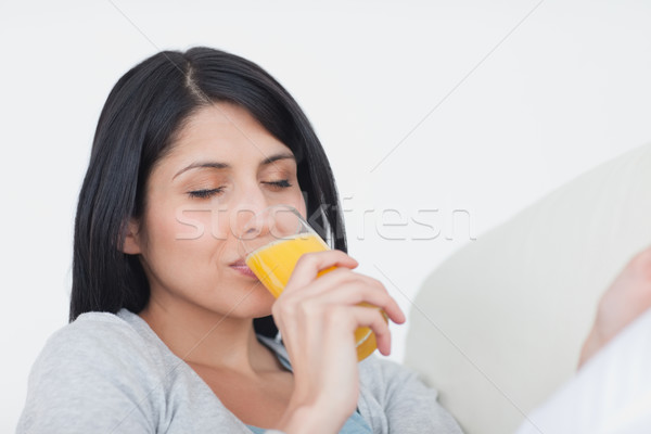 Woman closing her eyes while drinking a glass of orange juice in a living room Stock photo © wavebreak_media