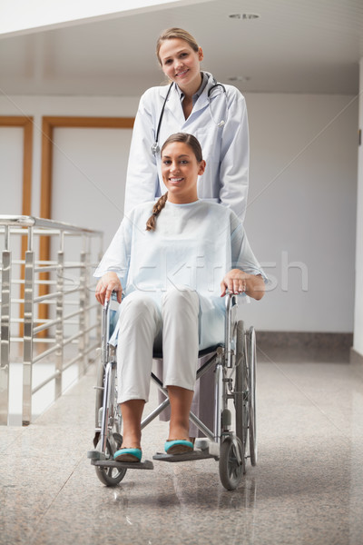 Doctor and patient looking at camera in hospital hallway Stock photo © wavebreak_media