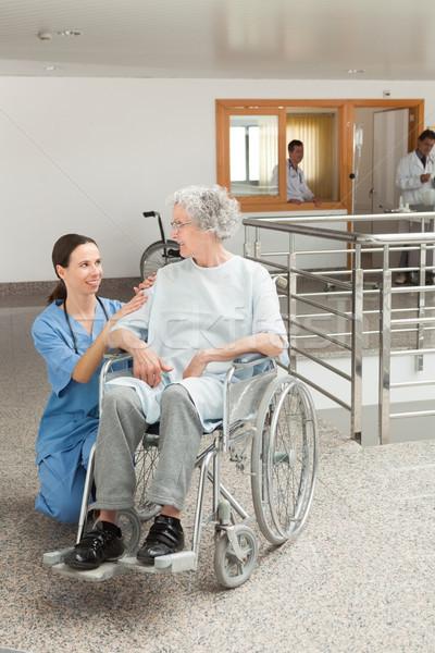 Nurse looking after old women sitting in wheelchair in hospital corridor Stock photo © wavebreak_media