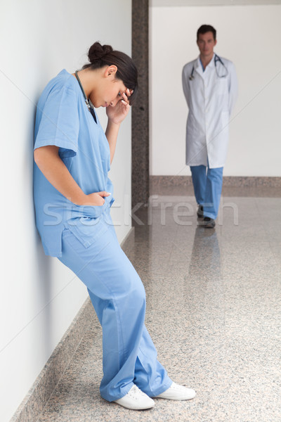 Sad urse leans against wall in hospital corridor with doctor approaching Stock photo © wavebreak_media