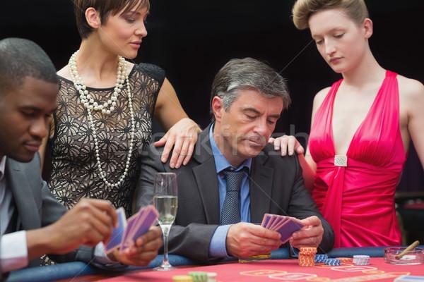Man playing poker with two women beside him in casino Stock photo © wavebreak_media
