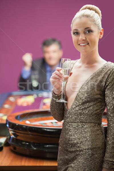 Mulher sorrindo champanhe vidro roleta homem Foto stock © wavebreak_media