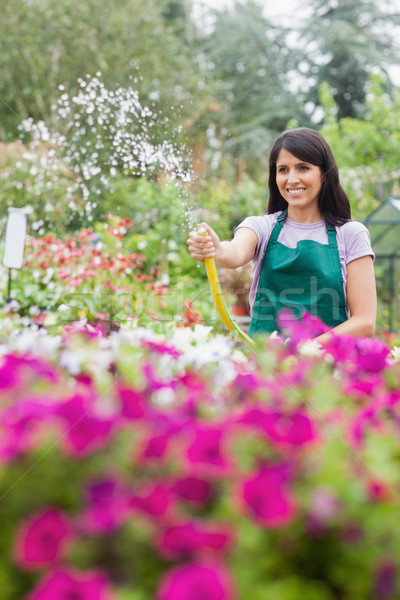 Woman having fun while watering plants in garden center with hose Stock photo © wavebreak_media