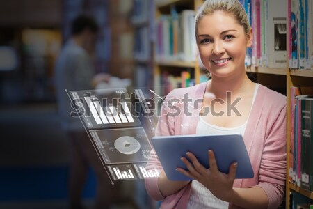 Woman leaning at a bookshelf holding a tablet pc while smiling in college library Stock photo © wavebreak_media
