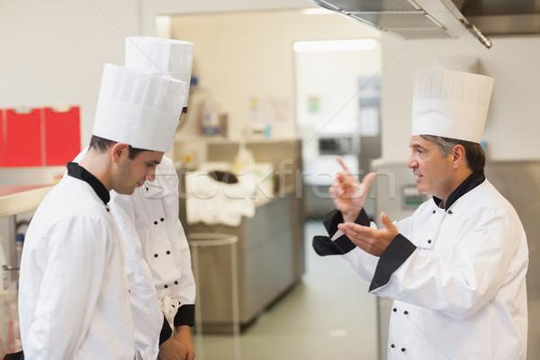 Upset head chef scolding employees in the kitchen Stock photo © wavebreak_media