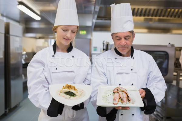 Chef's comparing chicken dishes in the kitchen Stock photo © wavebreak_media