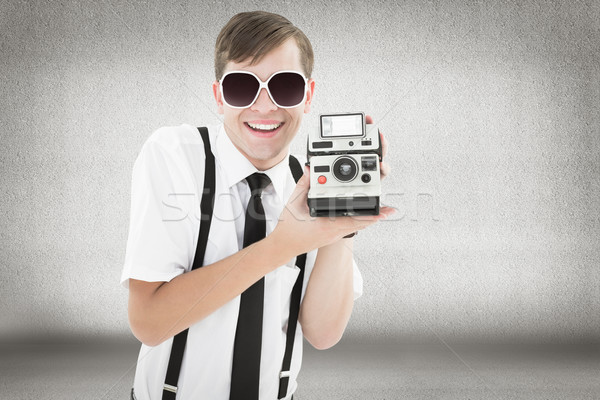 Composite image of geeky hipster holding a retro camera Stock photo © wavebreak_media