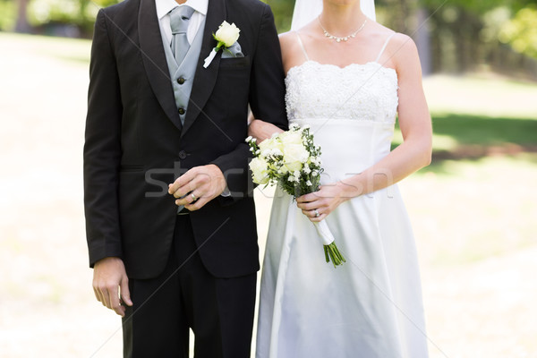 Friss házas pár kéz a kézben park középső rész virág Stock fotó © wavebreak_media