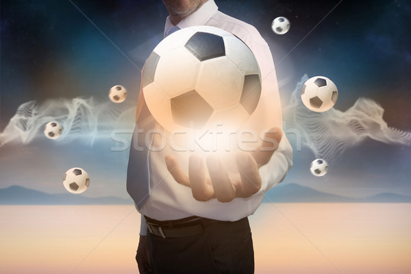 Businessman presenting floating footballs Stock photo © wavebreak_media