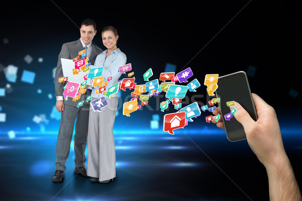 Hand holding smartphone with app icons and business partners beh Stock photo © wavebreak_media