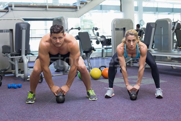 Bodybuilding man and woman lifting kettlebells in a squat  Stock photo © wavebreak_media