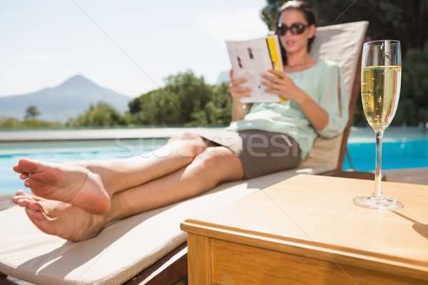 Woman reading book by pool with champagne in foreground Stock photo © wavebreak_media